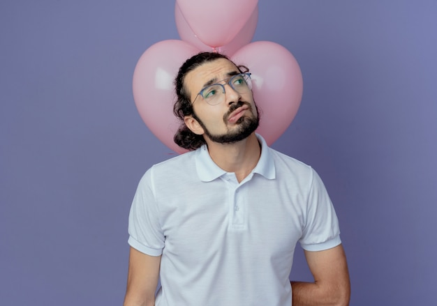 紫色の背景で隔離の前の風船に立っている眼鏡をかけて悲しいハンサムな男を見て