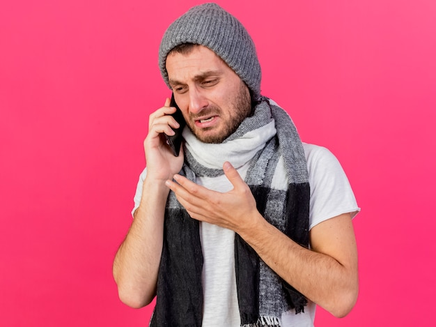スカーフと冬の帽子をかぶって悲しい若い病気の人の側を見てピンクの背景で隔離の電話で話します
