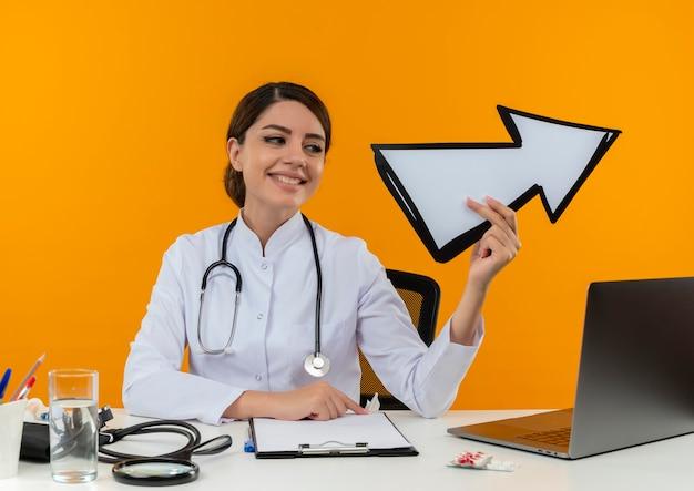 Глядя на сторону улыбается молодая женщина-врач в медицинском халате со стетоскопом, сидя за столом, работает на компьютере с медицинскими инструментами, держа знак направления на изолированной желтой стене