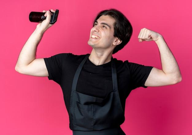 スプレーボトルを持ち、強いジェスチャーをしている制服を着た若いハンサムな男性床屋の笑顔の側を見る