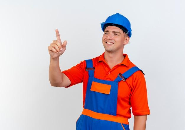 Глядя в сторону, улыбающийся молодой мужчина-строитель в униформе и защитном шлеме указывает сбоку