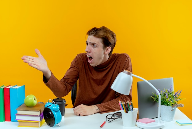 学校の道具を持って机に座っている驚いた若い学生の男の子を横から見て、手を左右に向ける