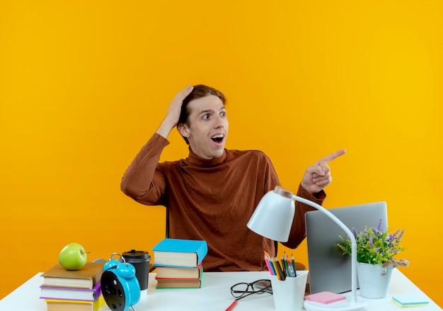 横を見て驚いた若い学生の男の子が机に座って、学校の道具を頭に置き、横を指さしている