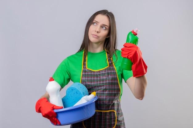 Глядя на сторону мышления, убирающую молодую женщину в униформе в красных перчатках, держащую чистящие инструменты на изолированной белой стене