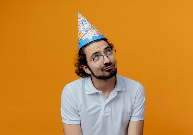 オレンジ色の背景に分離された眼鏡と誕生日の帽子を身に着けているハンサムな男を考える側を見て