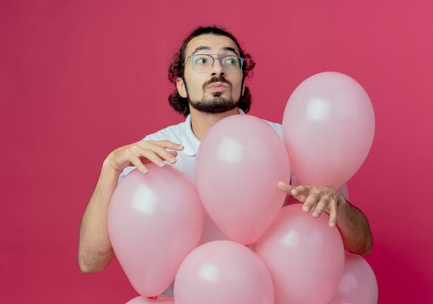 ピンクの背景に分離された風船の後ろに立っている眼鏡をかけてハンサムな男を考える側を見て