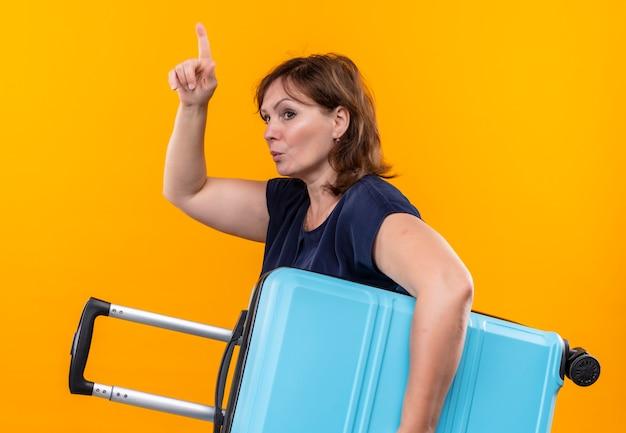 Женщина-путешественница средних лет, держащая чемодан, указывает на изолированную желтую стену
