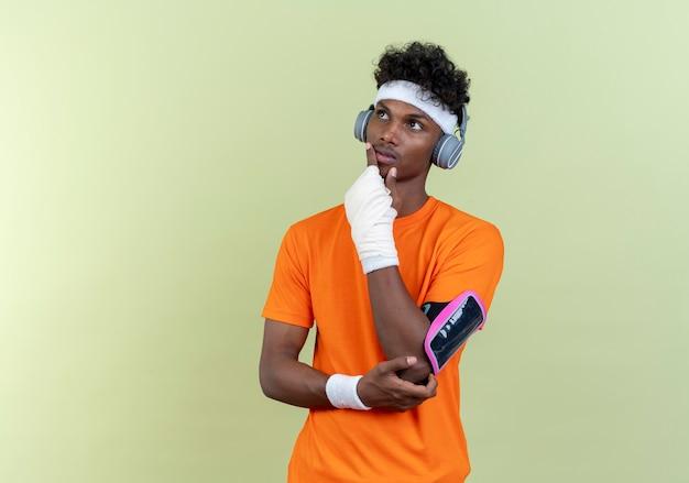 Глядя на стороннего мышления молодого афро-американского спортивного человека с повязкой на голову и браслетом и повязкой по телефону с наушниками, положив руку на подбородок