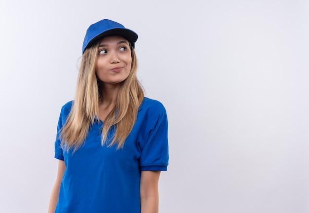파란색 유니폼과 모자를 입고 측면 생각 젊은 배달 소녀를 찾고 복사 공간이 흰 벽에 고립