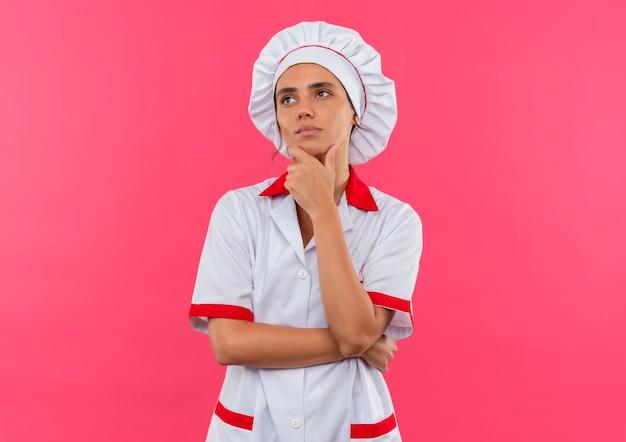 コピースペースと孤立したピンクの壁のあごに手を置くシェフの制服を着た若い女性料理人を考える側を見て