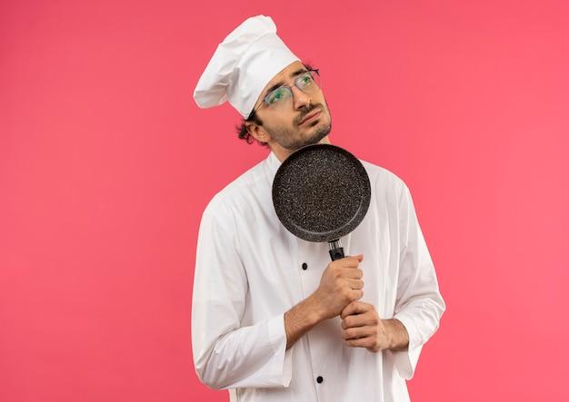 턱 주위에 프라이팬을 들고 요리사 유니폼과 안경을 착용하는 측면 생각 젊은 남성 요리사를 찾고