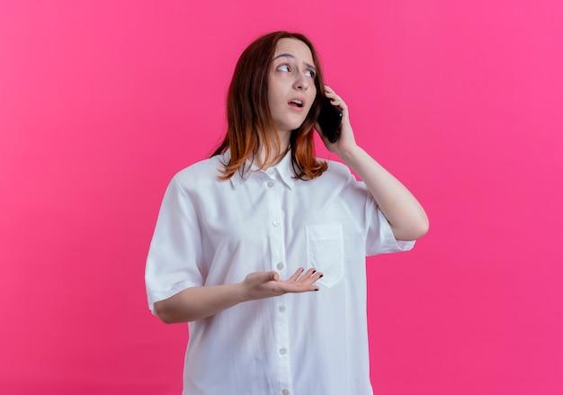 측면 생각보고 젊은 빨간 머리 소녀 복사 공간이 분홍색 배경에 고립 된 전화에 말한다