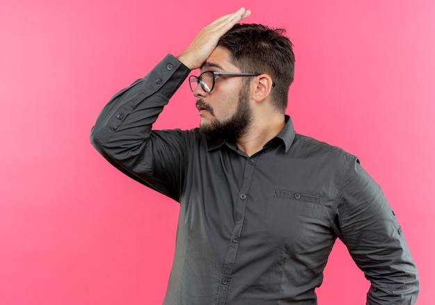 이마에 손을 넣어 안경을 쓰고 측면 불쾌한 젊은 사업가를보고