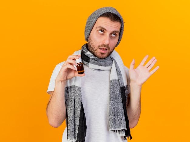 ガラス瓶に薬を保持し、黄色の背景で隔離の手を広げて冬の帽子とスカーフを身に着けている不機嫌な若い病気の人の側を見て
