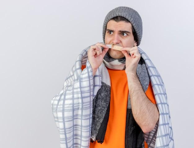 Глядя на сторону недовольного молодого больного человека в зимней шапке с шарфом, завернутым в плед, накладывая гипс на рот, изолированные на белом фоне