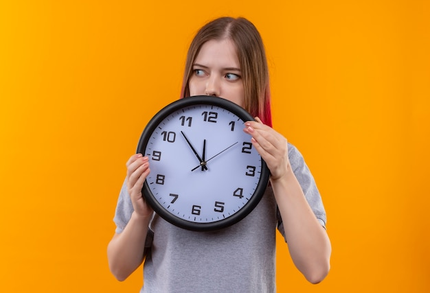 孤立した黄色の背景に壁時計を保持している灰色のtシャツを着ている若い美しい少女の側を見て
