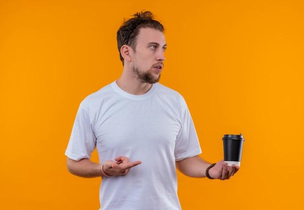 격리 된 오렌지 배경에 그의 손에 커피 한잔에 흰색 티셔츠 포인트를 입고 측면 젊은 남자를 찾고