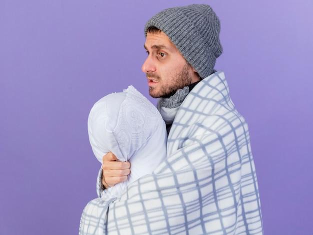 Глядя на сторону молодого больного человека в зимней шапке с шарфом, завернутым в клетчатую подушку, изолированную на фиолетовом фоне