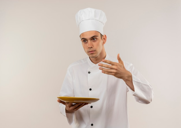 孤立した白い壁に彼の手で皿に何かを持っているふりをしているシェフの制服を着た若い男性料理人の側を見て