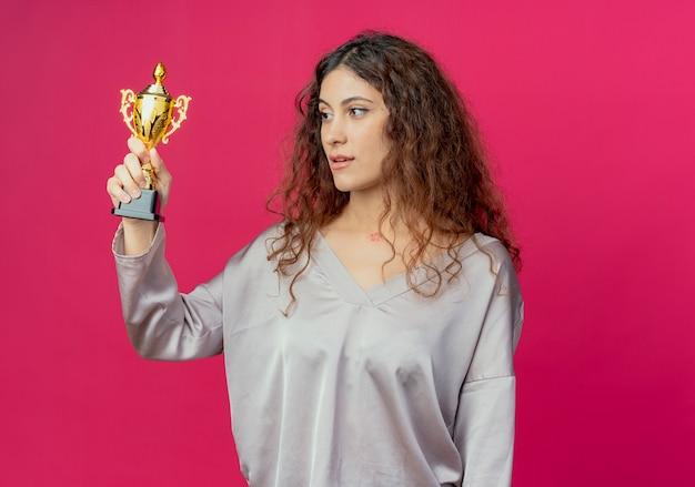 분홍색 벽에 고립 된 우승자 컵을 올리는 측면 젊은 예쁜 여자를 찾고