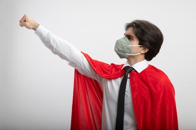 Глядя на сторону молодого парня супергероя в галстуке и медицинской маске, поднимающего кулак на белом фоне