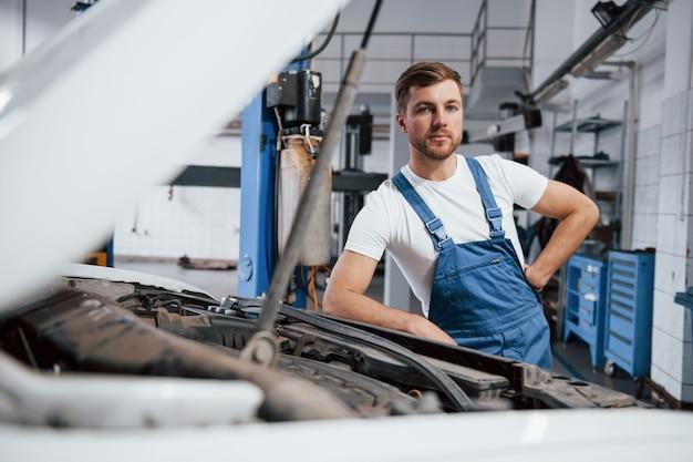 カメラを見てください。自動車のサロンで働く青い制服を着た従業員