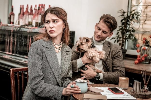 Смотрим на соседний стол. женщина чувствует ревность, пьет какао со своим партнером