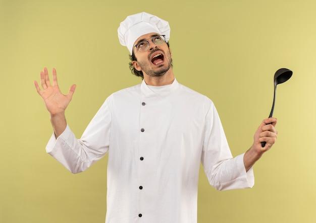シェフの制服とおたまと広げた手を持って眼鏡をかけている怒っている若い男性料理人を見上げる