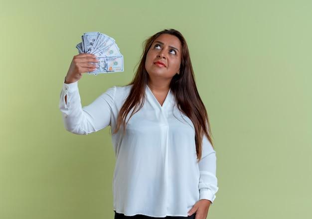 現金を持っているカジュアルな白人の中年女性を見上げる