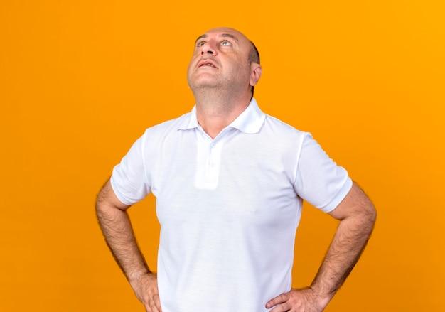 黄色の背景に分離された腰に手を置くカジュアルな成熟した男を見上げて