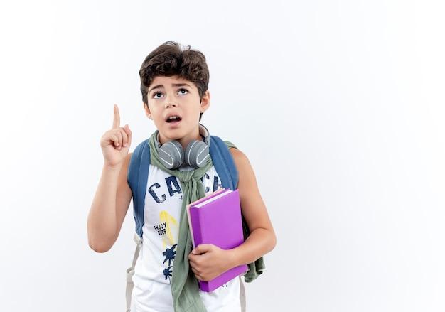 本を持ってバックパックとヘッドフォンを身に着けている心配している小さな男子生徒を見上げて