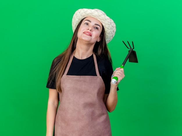 Глядя на впечатленную красивую девушку-садовника в униформе в садовой шляпе, держащую грабли с мотыгой, изолированную на зеленом