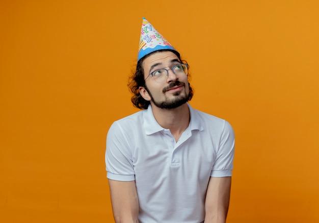 オレンジ色の背景に分離されたメガネと誕生日の帽子を身に着けている印象的なハンサムな男を見上げる