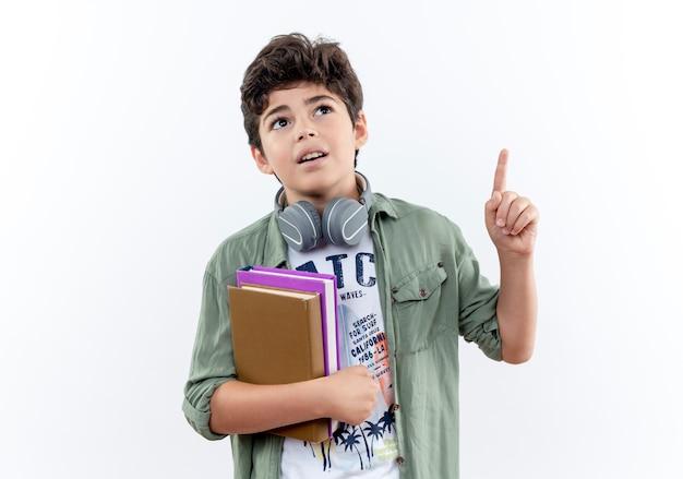 本を保持しているヘッドフォンを身に着けている感動の小さな男子生徒を見上げて、コピースペースで白い背景に分離された
