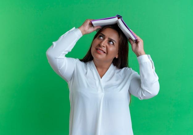 책으로 머리를 덮고 기쁘게 캐주얼 백인 중년 여성을 찾고
