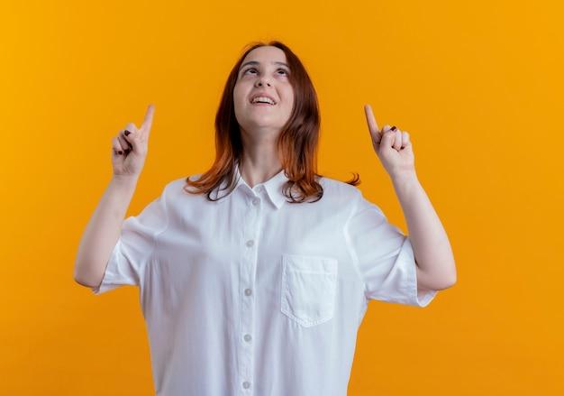 노란색에 고립 된 최대 만족 된 젊은 빨간 머리 여자 포인트를 찾고