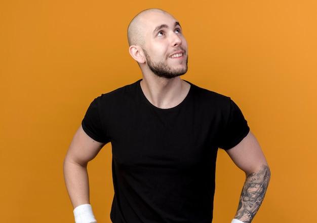 オレンジ色の背景で隔離の腰に手を置くリストバンドを身に着けている笑顔の若いスポーティな男を見上げる