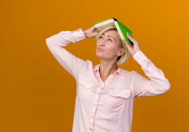 若い金髪のスラブの女性が本で頭を覆ったと思って見上げる