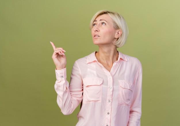 若いブロンドのスラブの女性が上を指していると考えて見上げる