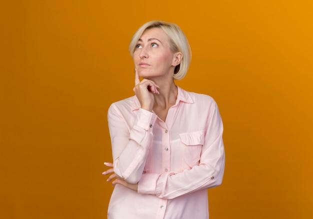 Глядя на вверх думает молодая блондинка славянская женщина положив палец на щеку