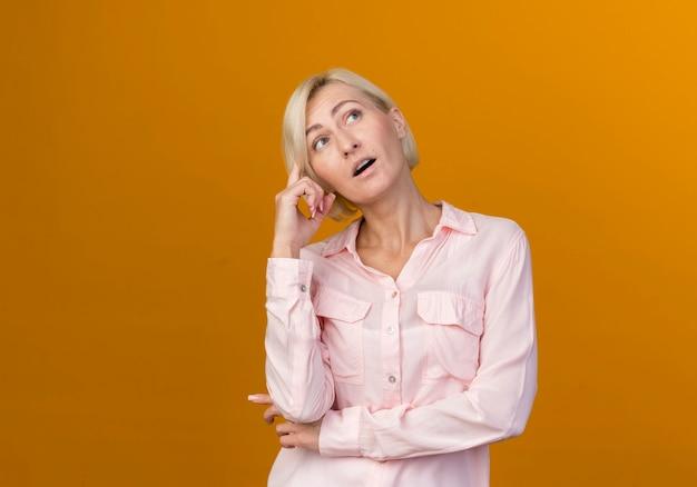 オレンジ色の壁に隔離された頭に指を置く若い金髪のスラブ女性を考えて見上げる
