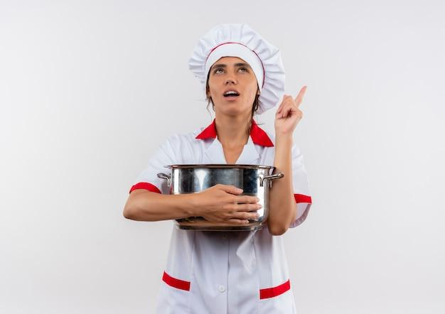 鍋を保持しているシェフの制服を着て、コピースペースのある孤立した白い壁を指している若い女性料理人を考えて見上げる