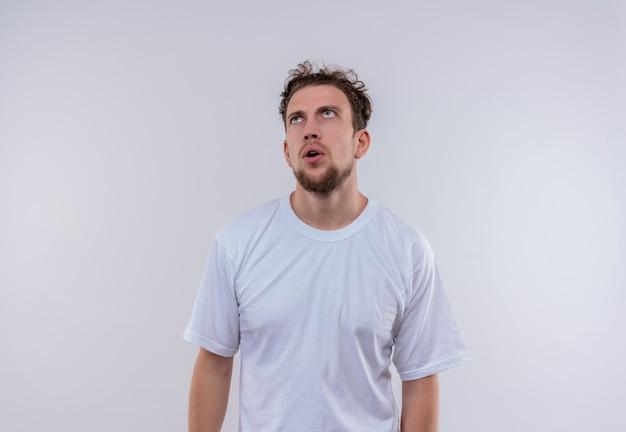 격리 된 흰색 배경에 흰색 티셔츠를 입고 생각 젊은 남자를 찾고