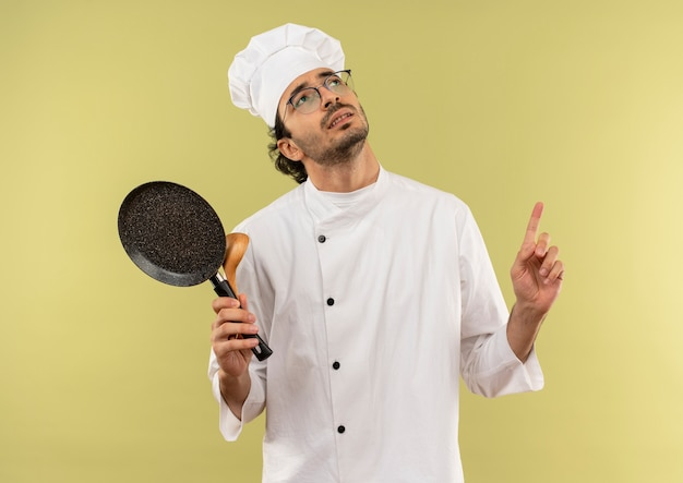 シェフの制服を着て、スプーンでフライパンを持って眼鏡をかけている若い男性料理人を考えて見上げる