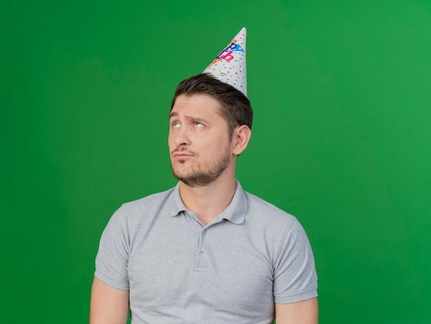 緑で隔離の誕生日のキャップを身に着けている思慮深い若いパーティーの男を見上げて