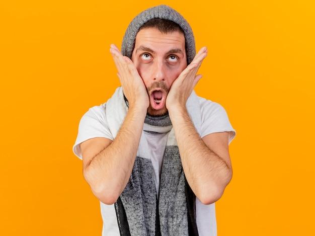 Глядя на недовольного молодого больного человека в зимней шапке и шарфе, положив руки на щеки, изолированные на желтом фоне