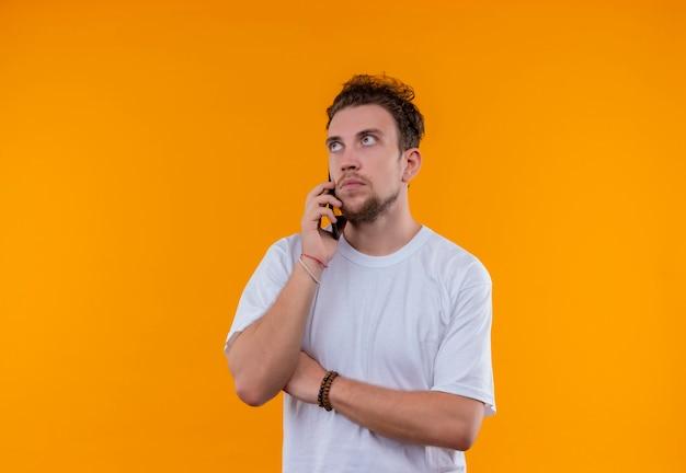 흰색 티셔츠를 입고 젊은 남자를 찾고 격리 된 오렌지 배경에 전화 건널목 손에 말한다