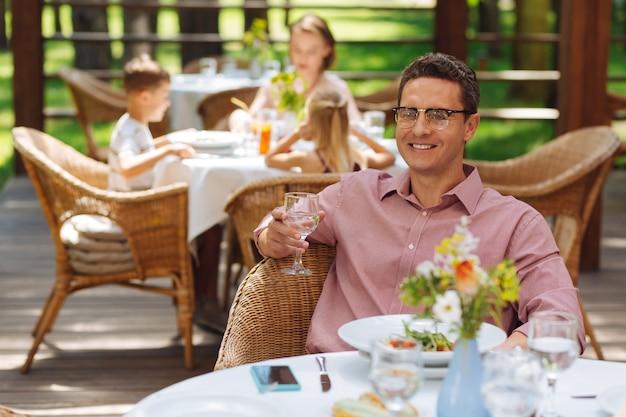 아내를보고 있습니다. 레스토랑에 앉아있는 동안 그의 사랑스러운 아름다운 아내를보고 즐거운 잘 생긴 남자