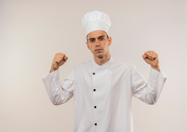 Looking at caamera young male cook wearing chef uniform doing strong gesture on isolated white wall with copy space