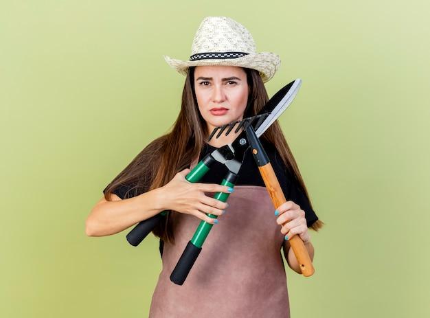 Guardando la fotocamera bella ragazza giardiniere in uniforme che indossa cappello da giardinaggio tenendo e tagliatori di attraversamento con rastrello isolato su sfondo verde oliva